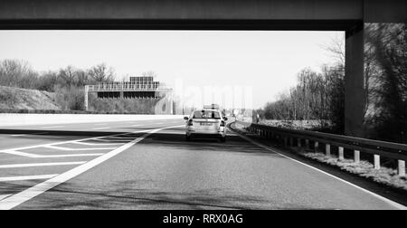 Germany - Feb 25, 2018: Wagon Skoda Octavia 4x4 car driving fast on winter day German Autobahn with the direction Offenburg, Basel, Frankfurt - black and white - Stock Photo