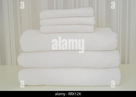 A pile of white fluffy towels in the closet. Service in the hotel concept. laundry - Stock Photo
