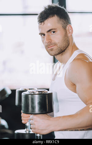 Muscular bodybuilder guy doing exercises with dumbbells in gym - Image - Stock Photo