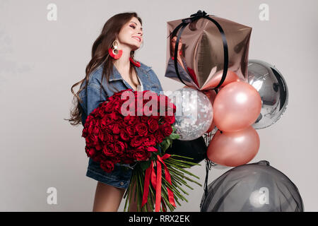 Beautiful young woman with bunch of roses and air balloons. - Stock Photo