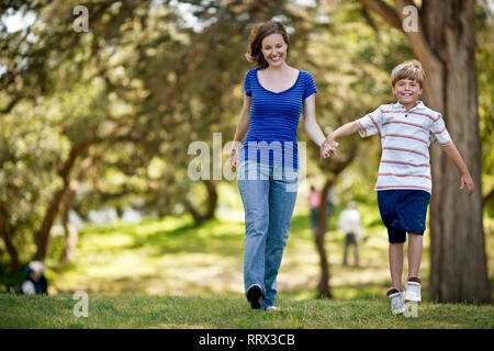 Boy holding his mother's hand as they walk through the park. - Stock Photo