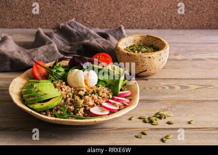Buckwheat porridge, boiled egg, fresh vegetables on a wooden wood table. Healthy balanced nutrition. Selective focus. - Stock Photo