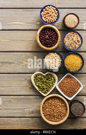 A set of various superfoods , whole grains,beans, seeds, legumes in bowls on a wooden plank table. Top view, copy space - Stock Photo