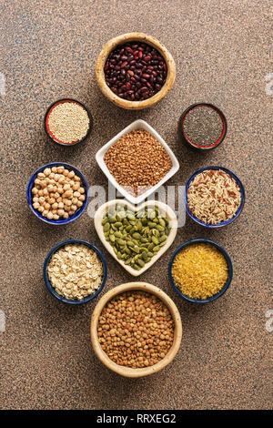 A set of various superfoods , whole grains,beans, seeds, legumes in bowls on a stone brown background. Top view. - Stock Photo
