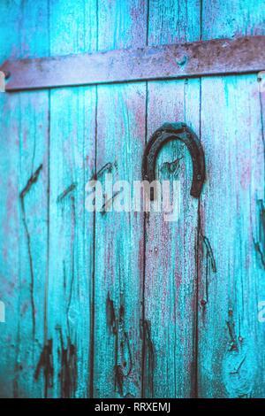 Old metal horseshoe hanging on blue wooden door - Stock Photo