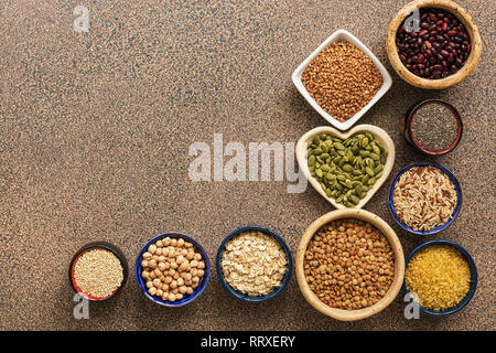 A variety of cereals, legumes, seeds on a brown stone background. Superfood set. View from above - Stock Photo