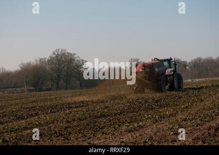 Muck Spreading on a farm with a tractor - Stock Photo