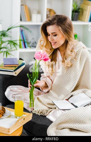 Romantic girl with knitted plaid sniffing pink flowers at home - Stock Photo