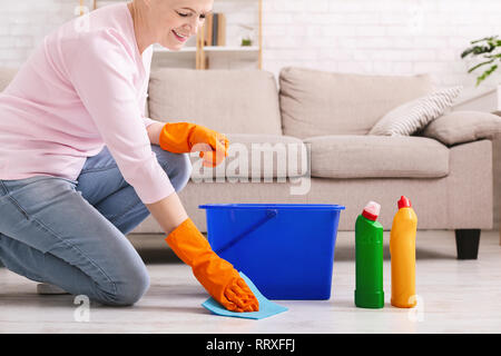 Smiling mature housewife cleaning floor at home - Stock Photo