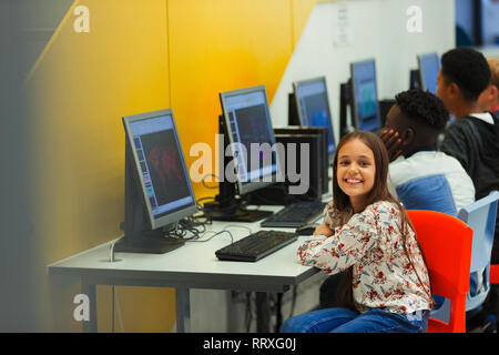 Portrait smiling, confident junior high girl student using computer in computer lab - Stock Photo