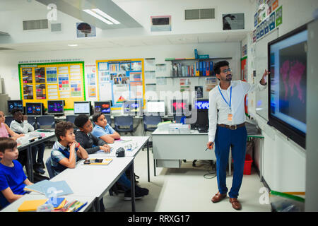 Male teacher leading lesson at touch screen in classroom - Stock Photo