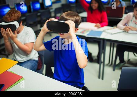 Junior high school boy students using virtual reality simulators in classroom - Stock Photo