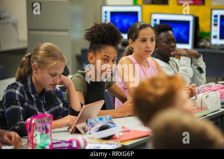 Focused junior high school girl student listening in classroom - Stock Photo