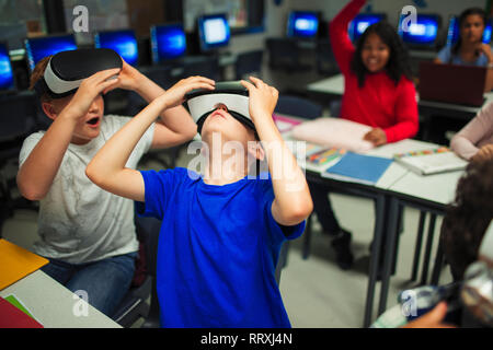 Curious junior high school boys using virtual reality simulators in classroom - Stock Photo