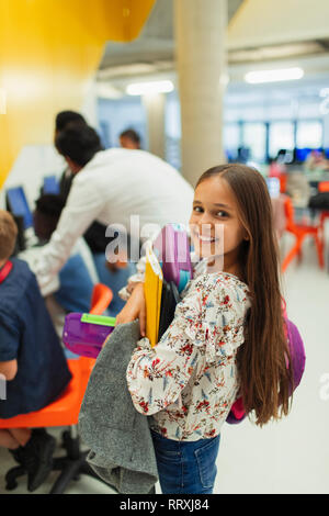 Portrait smiling, confident junior high girl student carrying books - Stock Photo