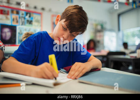 Focused junior high school boy student using highlighter, doing homework in classroom - Stock Photo