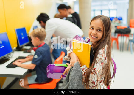 Portrait smiling, confident junior high girl student carrying books in library - Stock Photo