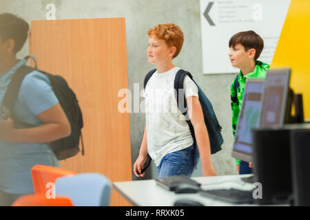 Junior high boy students walking in library - Stock Photo