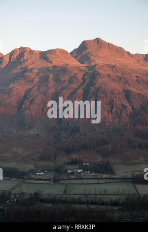 First light on Harrisons Stickle, one of the Langdale Pikes, seen over The Old Dungeon Ghyll Hotel, Lake District, UK