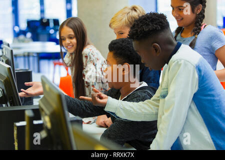 Junior high students using computer in library - Stock Photo