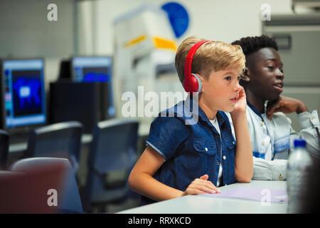 Focused junior high school boy with headphones in classroom - Stock Photo