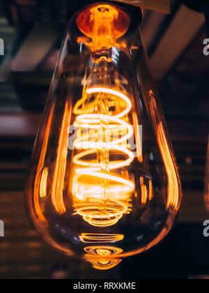 Bright glowing clear glass lamp pear shaped close up. Illumination edison retro lamp dark background. Antique vintage filament light bulb. - Stock Photo