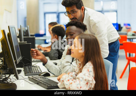 Teacher helping junior high students using computer in computer lab - Stock Photo