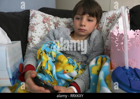 Sick child on couch watching television