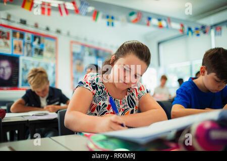 Focused junior high school girl student doing homework in classroom - Stock Photo