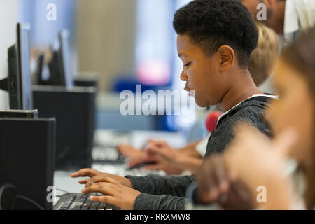 Focused junior high boy student using computer in computer lab - Stock Photo