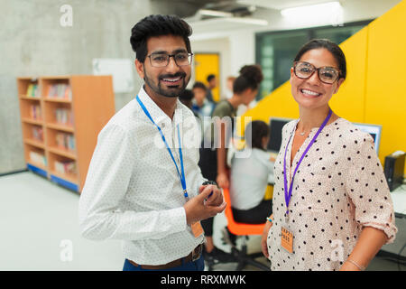 Portrait smiling, confident junior high teachers in library - Stock Photo