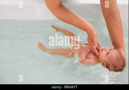 teaches infant baby to swim. Aquatic therapy for infant baby - Stock Photo