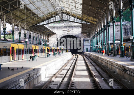 Porto, Portugal - December 2018: Sao Bento Train Station during quiet, sunny day, with commuters waiting for the train. - Stock Photo
