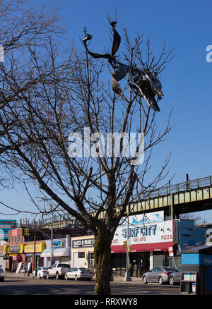 What appears to be a long strip, or strips, of plastic is wrapped around the bare winter branches of a tree on Surf Avenue at Coney Island in Brooklyn, New York, on a sunny February afternoon in 2019. Surf City restaurant and other business storefronts; the overhead railway of the Metropolitan Transportation Authority subway system; parked cars; and the shadows of Luna Park's historic wooden Cyclone roller coaster (out of view on the left) falling on the roadway (pavement) form street scenery in the bottom third of the background of this peninsular community, with blue sky in the rest. - Stock Photo