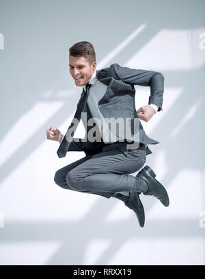 Full-length jump of a young man jumping with an open mouth, isolated on a white background. - Stock Photo