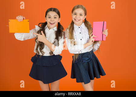 Pointing finger at book cover. Small girls with workbooks for writing. Cute schoolgirls holding lesson books. School children learn reading books. Little children with school diaries for making notes. - Stock Photo