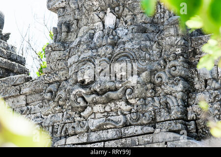 Traditional scary looking Bali island stone sculpture on ancient wall - Stock Photo