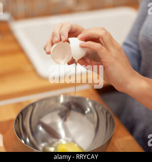 woman breaking the egg in the metal plate and preparing for making the cake - Stock Photo