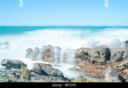Waves smoothed by long exposure washing in around rocky foreshore at base of Mount Maunganui, Tauranga New Zealand - Stock Photo