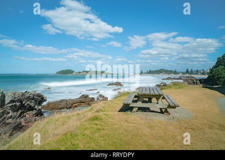 Outdoor table beside walking track with distant waves smoothed by long exposure washing in around rocky foreshore at base of Mount Maunganui, Tauranga - Stock Photo