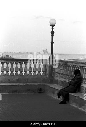 Griechenland, Greece - Eine ältere Frau sitzt an den Hafenanlagen und schaut auf den Hafen. Elder woman sitting by the harbour. - Stock Photo