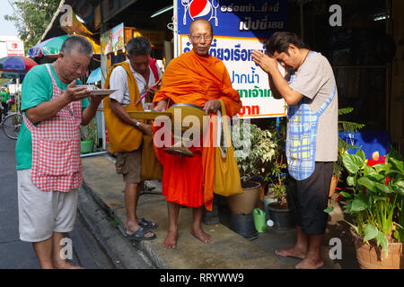 Local shopkeepers in Thonburi, Bangkok, Thailand, praying to a Buddhist monk during his traditional morning alms round - Stock Photo