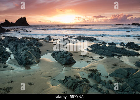 Sunset on the rocky beach at Hartland Quay on the north coast of Devon - Stock Photo