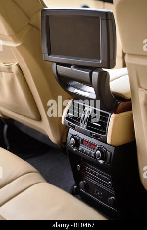 Car inside. Interior in cream colors leather of prestige luxury modern car. Swivel display for back seats passenger with media control panel vertical