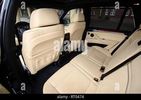 Car inside. Interior in cream colors leather of prestige luxury modern car. Swivel display for back seats passenger with media control panel