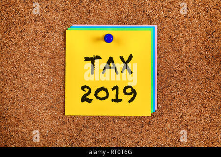 Post-it notes with reminder Tax 2019 on corkboard. Close-up. - Stock Photo