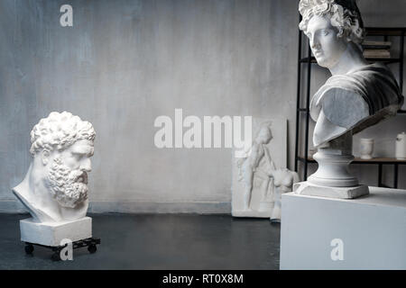 God Apollo bust sculpture and bust of the Farnese Hercules. Head sculpture, plaster copy of a marble statues of Greek gods and heroes on grange - Stock Photo