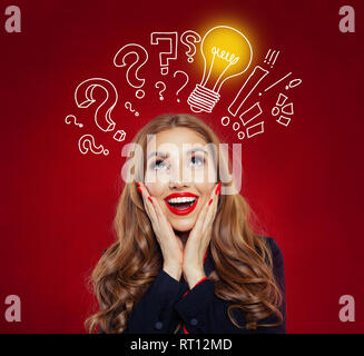 Happy surprised woman looking up at yellow lightbulb on red background. Brainstorm, ideas, problem and solution concept. Positive emotions, facial exp