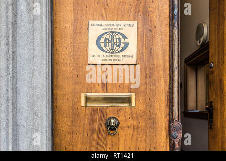 Ixelles, Brussels / Belgium - 02 20 2019: Old wooden entrance door and indication sign of the National geographic Institute at the site of La Cambre - Stock Photo