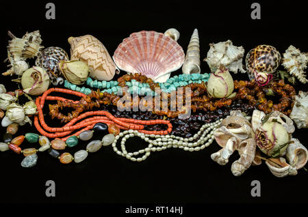 Beads of turquoise, red coral, amber, garnet stone, multi-colored agate, pearls among various shells and dry buds on a black background - Stock Photo